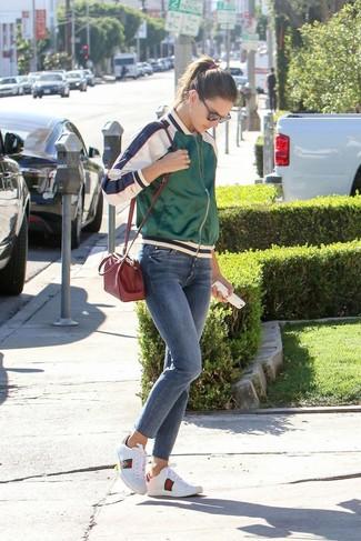 Как и с чем носить: зеленый сатиновый бомбер, белая футболка с круглым вырезом, синие джинсы скинни, белые кожаные низкие кеды с принтом