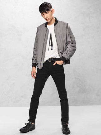 Как и с чем носить: серый бомбер, бело-черная футболка с круглым вырезом с принтом, черные джинсы, черные кожаные низкие кеды