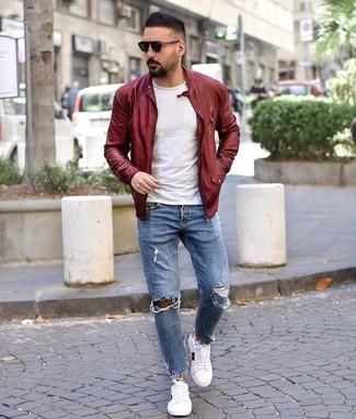 Как и с чем носить: темно-красный кожаный бомбер, белая футболка с круглым вырезом, голубые рваные джинсы, белые низкие кеды с принтом
