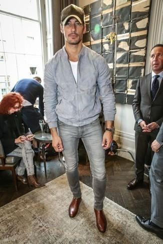 Серый замшевый бомбер: с чем носить и как сочетать мужчине: Ансамбль из серого замшевого бомбера и серых джинсов позволит подчеркнуть твою индивидуальность. Не прочь сделать образ немного строже? Тогда в качестве обуви к этому луку, выбери коричневые кожаные ботинки челси.