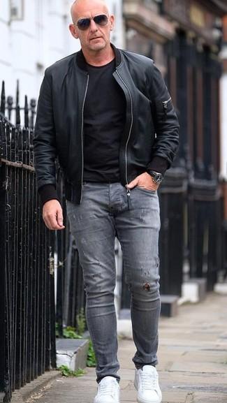 Как и с чем носить: черный кожаный бомбер, черная футболка с круглым вырезом, серые рваные зауженные джинсы, белые кожаные низкие кеды