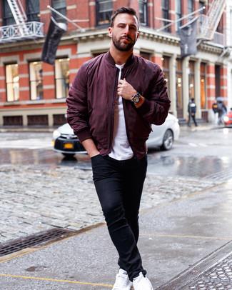 Как и с чем носить: темно-красный бомбер, белая футболка с круглым вырезом, черные зауженные джинсы, белые кожаные низкие кеды