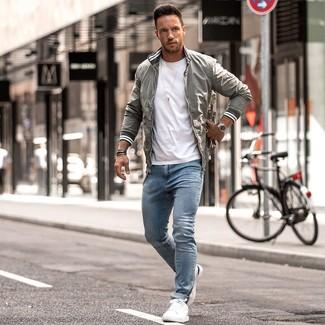 Как и с чем носить: серый бомбер, белая футболка с круглым вырезом, голубые зауженные джинсы, белые кожаные низкие кеды