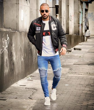 Как и с чем носить: черный бомбер с принтом, белая футболка с круглым вырезом с принтом, синие зауженные джинсы, белые кожаные низкие кеды