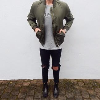 Как и с чем носить: оливковый бомбер, серая футболка с круглым вырезом с принтом, черные рваные зауженные джинсы, черные кожаные ботинки челси