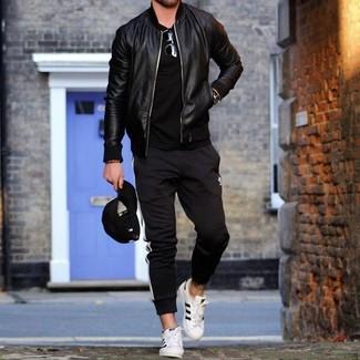 Как и с чем носить: черный кожаный бомбер, черная футболка с круглым вырезом, черно-белые спортивные штаны в вертикальную полоску, белые кожаные низкие кеды