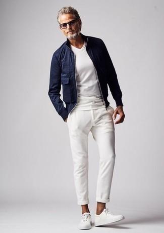 Как одеваться мужчине за 50: Темно-синий бомбер и белые брюки чинос будет отличной идеей для простого образа на каждый день. Создать интересный контраст с остальными вещами из этого образа помогут белые кожаные низкие кеды.