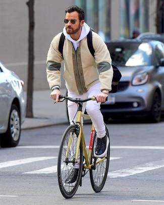 Как и с чем носить: бежевый флисовый бомбер, белый худи, белые джинсы, черные кожаные низкие кеды