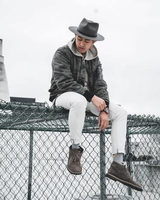 С чем носить темно-серую шерстяную шляпу мужчине: Сочетание темно-серого бомбера с камуфляжным принтом и темно-серой шерстяной шляпы особенно популярно среди ценителей комфорта. Хочешь сделать ансамбль немного элегантнее? Тогда в качестве дополнения к этому луку, стоит обратить внимание на темно-коричневые замшевые ботинки дезерты.