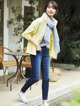 Как и с чем носить: желтая ветровка, темно-синие джинсы скинни, белые низкие кеды из плотной ткани, светло-коричневая соломенная большая сумка