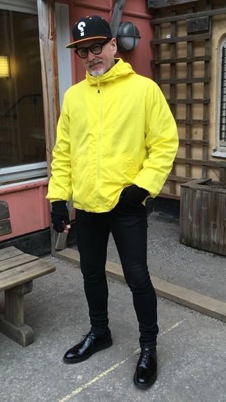 Как и с чем носить: желтая ветровка, черные зауженные джинсы, черные кожаные туфли дерби, черная бейсболка с принтом