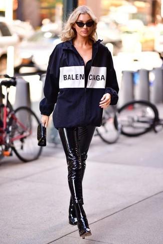 Как и с чем носить: темно-синяя ветровка с принтом, черные кожаные узкие брюки, черные кожаные ботильоны, черный кожаный клатч