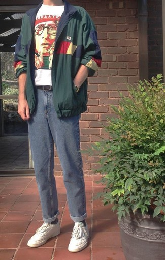 Как и с чем носить: темно-зеленая ветровка, бело-красная футболка с круглым вырезом с принтом, синие джинсы, белые кожаные низкие кеды