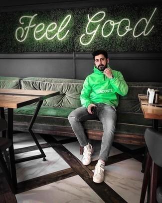 Мужские луки: Зеленая ветровка и серые рваные джинсы — стильный выбор молодых людей, которые никогда не сидят на месте. Думаешь сделать ансамбль немного элегантнее? Тогда в качестве обуви к этому луку, выбери бело-черные низкие кеды из плотной ткани.
