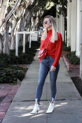 Как и с чем носить: красная водолазка, синие джинсы скинни, белые кожаные ботильоны, красная кожаная стеганая сумка-саквояж