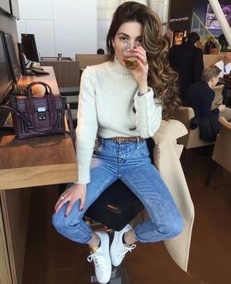 Как и с чем носить: белая вязаная водолазка, синие джинсы скинни, белые кожаные низкие кеды, темно-пурпурная кожаная сумка-саквояж