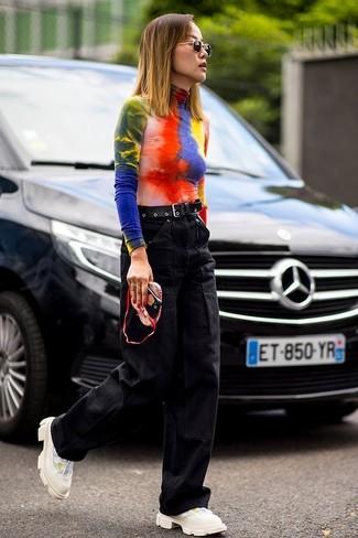 Как и с чем носить: разноцветная водолазка c принтом тай-дай, черные джинсовые широкие брюки, бежевые кроссовки, черный кожаный ремень