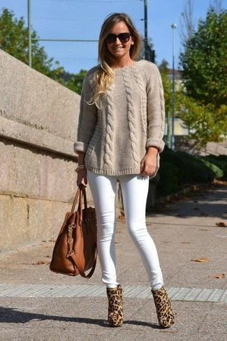 Как и с чем носить: бежевый вязаный свитер, белые джинсы скинни, светло-коричневые ботильоны из ворса пони с леопардовым принтом, коричневая кожаная большая сумка