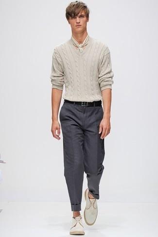 Бежевый вязаный свитер и темно-серые классические брюки — необходимые вещи в классическом мужском гардеробе. Любители рискованных вариантов могут дополнить образ бежевыми замшевыми дезертами.