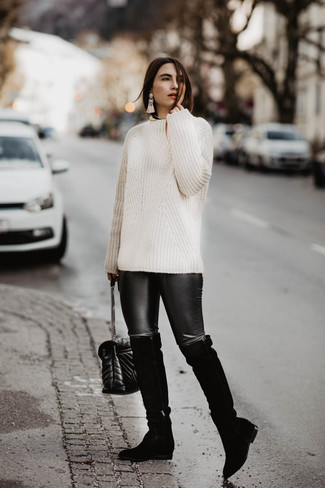 Как и с чем носить: белый вязаный свитер, черные кожаные леггинсы, черные замшевые ботфорты, черная кожаная стеганая сумка через плечо