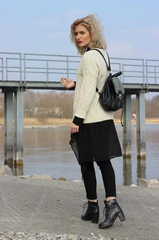 Как и с чем носить: бежевый вязаный свитер, черная шифоновая туника, черные джинсы скинни, черные кожаные ботильоны на шнуровке