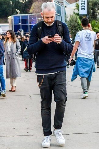 Темно-серые рваные джинсы: с чем носить и как сочетать мужчине: Если у тебя планируется суматошный день, сочетание темно-синего вязаного свитера и темно-серых рваных джинсов позволит создать комфортный ансамбль в стиле кэжуал. Не прочь сделать лук немного строже? Тогда в качестве обуви к этому луку, выбирай белые кожаные низкие кеды.