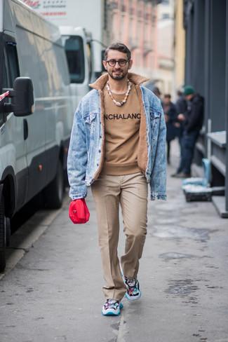 Как и с чем носить: голубая джинсовая куртка, светло-коричневый свитер с круглым вырезом с принтом, светло-коричневые классические брюки, разноцветные кроссовки