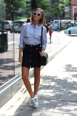 Как и с чем носить: голубая классическая рубашка в вертикальную полоску, черная юбка на пуговицах, бело-черные кожаные низкие кеды, черная кожаная сумка через плечо