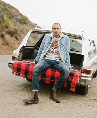 Как и с чем носить: голубая джинсовая короткая дубленка, серый свитер с круглым вырезом с принтом, темно-бирюзовые джинсы, коричневые кожаные ботинки челси