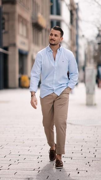 Модные мужские луки 2020 фото в теплую погоду: Сочетание голубой рубашки с длинным рукавом и светло-коричневых брюк чинос вне всякого сомнения будет обращать на себя взгляды прекрасных барышень. В сочетании с этим образом отлично будут выглядеть темно-коричневые кожаные топсайдеры.