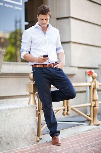 Голубая рубашка с длинным рукавом в клетку и темно-синие брюки чинос — необходимые вещи в арсенале стильного мужчины. Коричневые кожаные броги добавят элемент классики в твой образ.