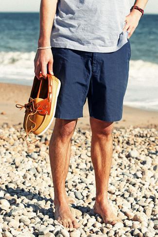 Если ты делаешь ставку на комфорт и практичность, голубая футболка с v-образным вырезом в горизонтальную полоску и темно-синие шорты — классный вариант для модного повседневного мужского ансамбля. Думаешь привнести в этот ансамбль толику строгости? Тогда в качестве обуви к этому образу, обрати внимание на оранжевые кожаные топсайдеры.