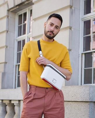 Как и с чем носить: горчичная вязаная футболка с круглым вырезом, розовые брюки чинос, белая поясная сумка