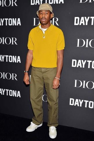 Как и с чем носить: горчичная футболка-поло, оливковые брюки чинос, белые кожаные низкие кеды, бежевая панама