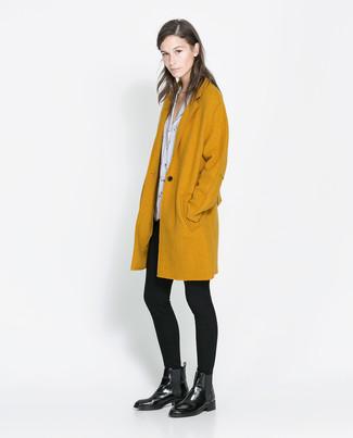 Как и с чем носить: горчичное пальто, бело-черная блуза с коротким рукавом с принтом, черные леггинсы, черные кожаные ботинки челси