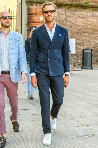 Темно-синий двубортный пиджак: с чем носить и как сочетать мужчине: Несмотря на то, что это весьма консервативный образ, дуэт темно-синего двубортного пиджака и темно-синих классических брюк всегда будет по душе стильным мужчинам, но также покоряет при этом сердца дам. Если сочетание несочетаемого привлекает тебя не меньше, чем проверенная классика, дополни свой лук белыми кожаными низкими кедами.
