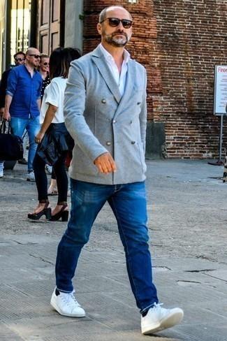 Модные мужские луки 2020 фото: Серый двубортный пиджак и синие джинсы — прекрасный выбор для воплощения мужского лука в стиле смарт-кэжуал. Почему бы не привнести в этот лук чуточку легкой небрежности с помощью белых кожаных низких кед?