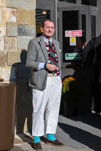 Как одеваться мужчине за 60: Хочешь выглядеть престижно? Тогда дуэт серого шерстяного двубортного пиджака и белых брюк чинос - это то, что тебе нужно. Такой образ легко получает новое прочтение в тандеме с темно-коричневыми замшевыми лоферами.