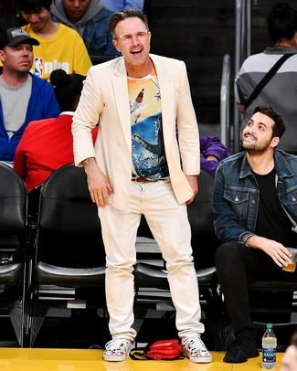 Как и с чем носить: бежевый двубортный пиджак, разноцветная футболка с круглым вырезом с принтом, бежевые джинсы, белые низкие кеды из плотной ткани с принтом