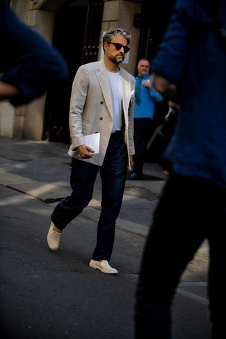 Мужские луки в жару: Бежевый льняной двубортный пиджак и темно-синие классические брюки позволят составить выразительный мужской лук. Поклонники незаезженных вариантов могут закончить образ бежевыми слипонами из плотной ткани.