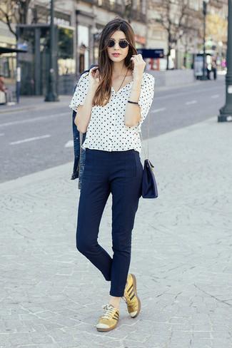 Как и с чем носить: синяя джинсовая куртка, бело-черная блуза с коротким рукавом в горошек, темно-синие узкие брюки, золотые кожаные низкие кеды