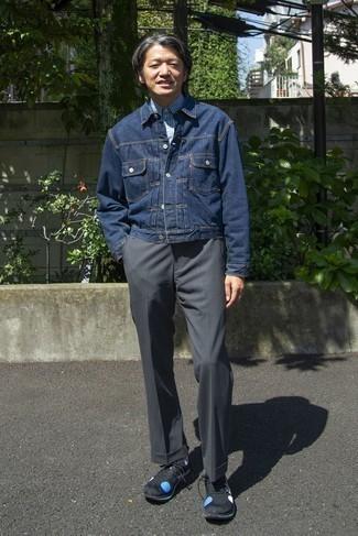 Как одеваться мужчине за 50: Несмотря на свою несложность, дуэт темно-синей джинсовой куртки и темно-серых брюк чинос неизменно нравится стильным мужчинам, покоряя при этом сердца представительниц прекрасного пола. Любишь дерзкие сочетания? Дополни свой лук черно-синими кроссовками.