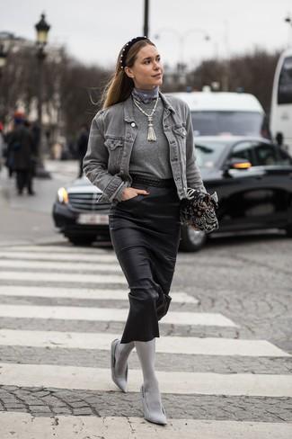 Как и с чем носить: серая джинсовая куртка, серый свитер с круглым вырезом, черная кожаная юбка-миди, серые туфли из плотной ткани