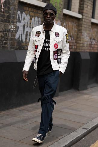 Как и с чем носить: белая джинсовая куртка с вышивкой, черно-белая футболка с круглым вырезом с принтом, темно-синие брюки чинос, черные низкие кеды из плотной ткани