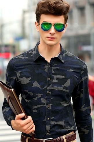 Как и с чем носить: темно-синяя джинсовая рубашка с камуфляжным принтом, светло-коричневые брюки чинос, темно-коричневый кожаный мужской клатч, темно-коричневый кожаный ремень