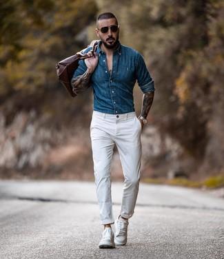Коричневая кожаная дорожная сумка: с чем носить и как сочетать мужчине: Синяя джинсовая рубашка и коричневая кожаная дорожная сумка — великолепная формула для воплощения приятного и практичного ансамбля. Белые кожаные низкие кеды добавят луку немного консерватизма.