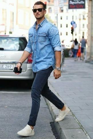 Голубая джинсовая рубашка: с чем носить и как сочетать мужчине: Если ты любишь выглядеть с иголочки, и при этом чувствовать себя комфортно и уверенно, опробируй это сочетание голубой джинсовой рубашки и темно-синих джинсов. Белые кожаные низкие кеды — отличный выбор, чтобы завершить лук.