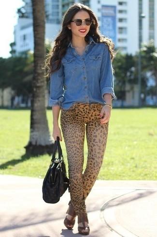 Как и с чем носить: синяя джинсовая рубашка, светло-коричневые джинсы скинни с леопардовым принтом, коричневые кожаные босоножки на каблуке, черная кожаная большая сумка