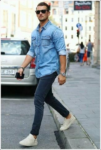 Как и с чем носить: синяя джинсовая рубашка, темно-синие зауженные джинсы, бежевые низкие кеды, черные солнцезащитные очки