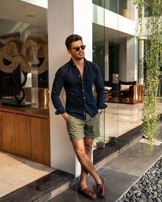Модный лук: темно-синяя джинсовая рубашка, оливковые шорты, коричневые кожаные топсайдеры, коричневые солнцезащитные очки